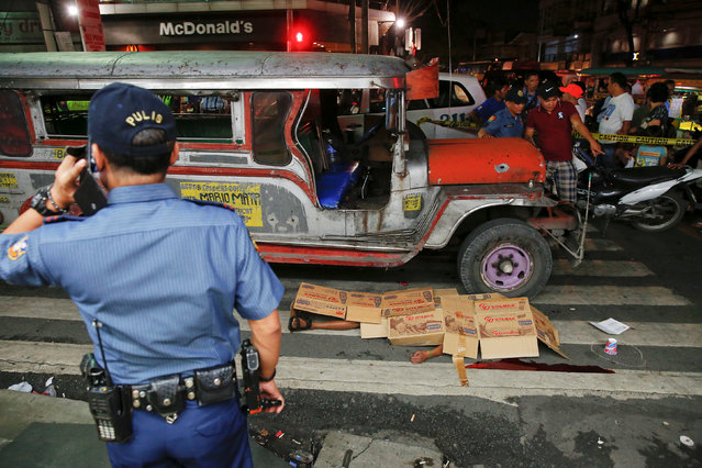 The body of a man killed by unknown gunmen is covered as police investigates the scene in Manila, Ph
