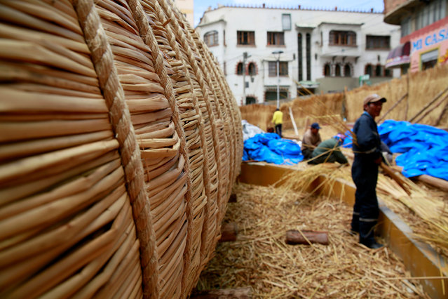 "Aymara builders work on the ""Viracocha III"", a boat made only from the totora reed, as it is being p"