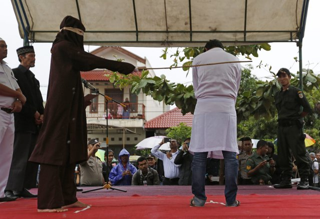 An Acehnese man is being whipped in front of the public at Baiturrahman Grand Mosque, Banda Aceh, In