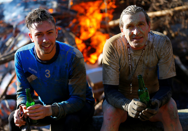 Competitors relax in front of a fire after finishing the Wildsau Dirt Run (Wild Boar Dirt Run) obsta