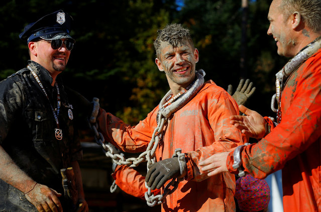 Competitors in costumes smile after finishing the Wildsau Dirt Run (Wild Boar Dirt Run) obstacle cou