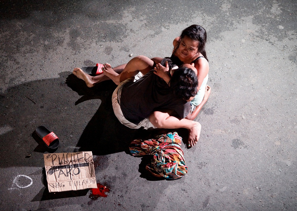 A woman cradles the body of her husband, who was killed on a street by a vigilante group, according to police, in a spate of drug related killings in Pasay city, Metro Manila