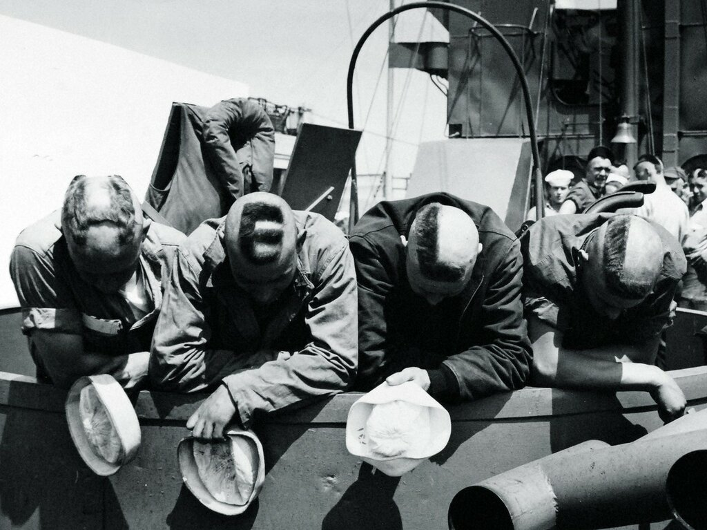 Four Coast Guardsmen, serving as scouts and proceeding in an LCM. They subjected their knobs to the shearing just to kill time in the English Channel crossing, June 1944.