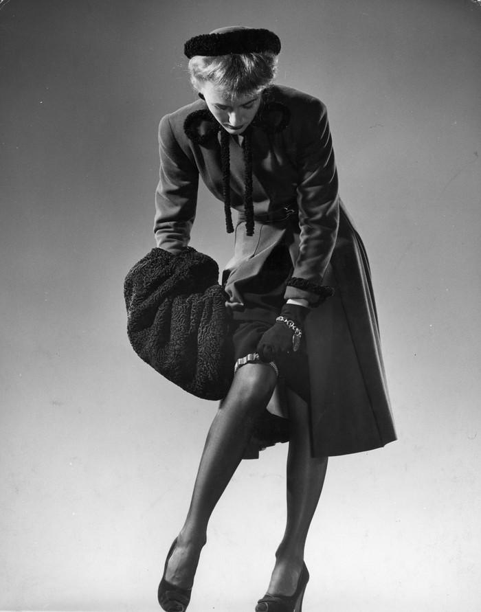 6. Модель в черных чулках, пальто, шляпке с мехом и меховой муфте поправляет подвязку. 1946 год. (Gj