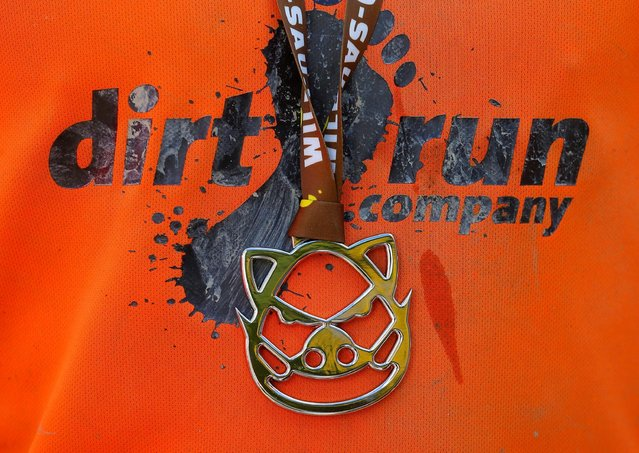 A finisher's medal hangs over the shirt of a competitor after the Wildsau Dirt Run (Wild Boar D