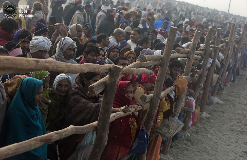 Мужчины и женщины на берегу наблюдают за купанием «святых». (REUTERS/Ahmad Masood)