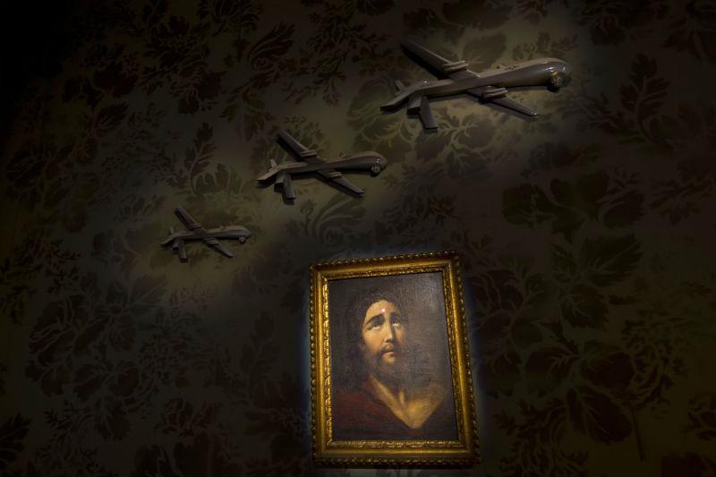 Одна из стен декорирована моделями дронов и портретом Иисуса со снайперским прицелом на лбу.