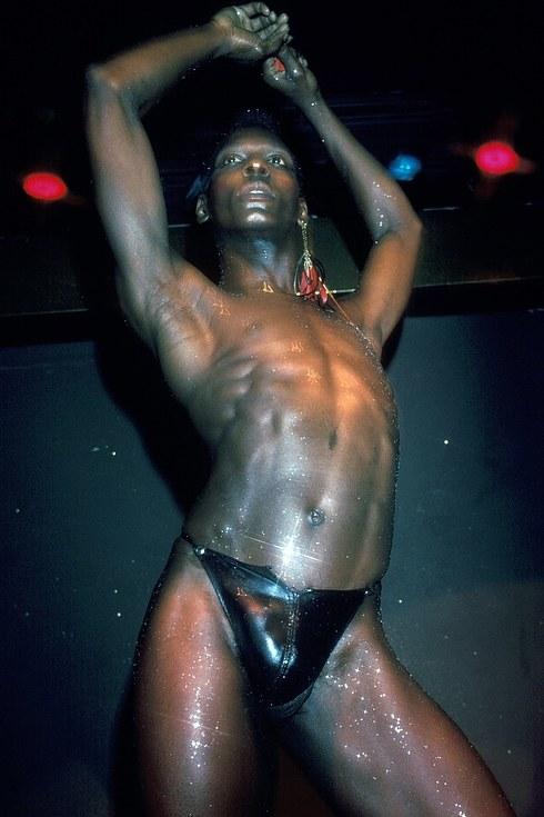 Мужчина в кожаных стрингах, обсыпанный блестками, исполняет танец в клубе Electric Circus в Нью-Йорк