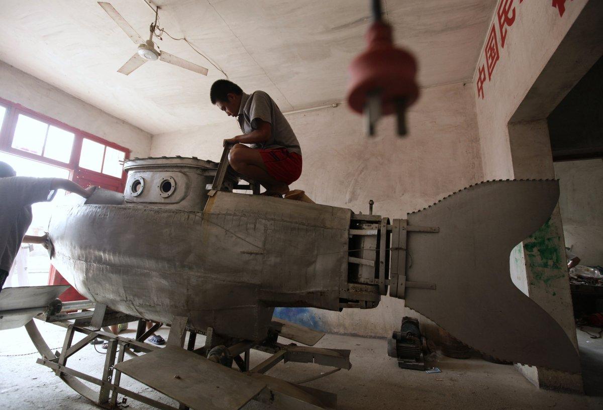 23. Рабочий полирует поверхность незаконченной миниатюрной подлодки в мастерской местного кустаря-из