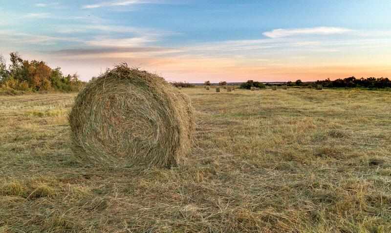 Синее небо и тюк сена на поле