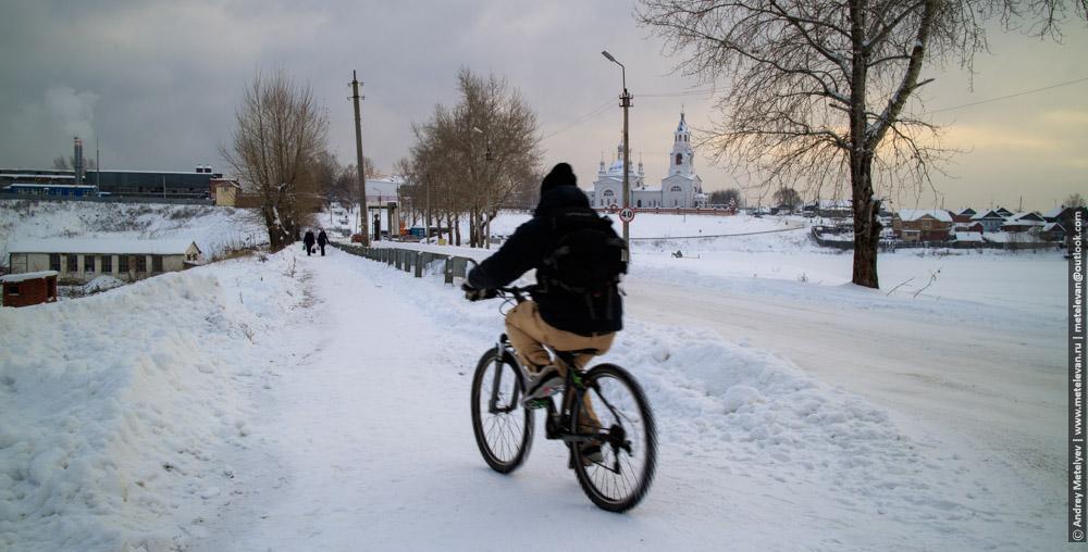 велосипедист зимой в поселке Новоуткинск на фоне церкви