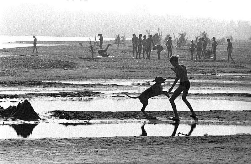 Подросток играет с собакой на пляже. СССР, Башкирия, 1978 год.