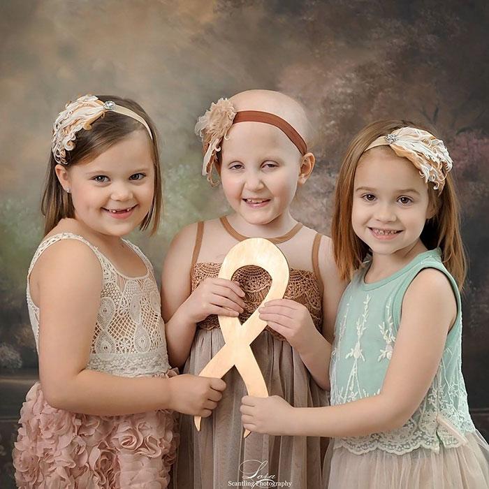 Золотая лента, которую держат девочки, — символ борьбы с детской онкологией.