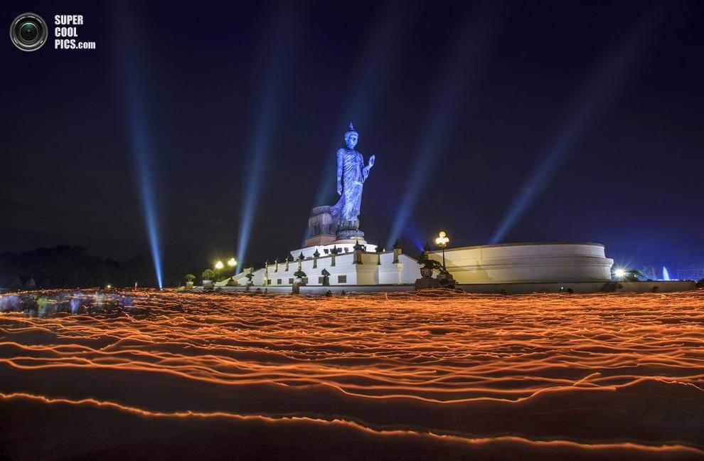 Верующие со свечами в руках на фоне Статуи Будды в провинции Наконпатом, Таиланд. (Athit Perawon