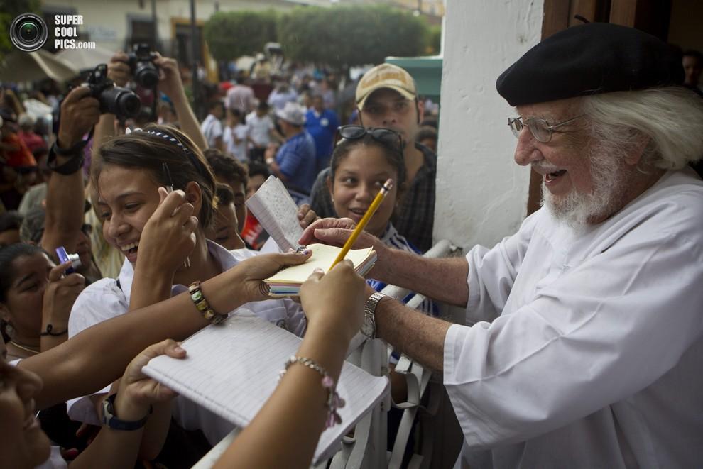 Эрнесто Карденаль раздает автографы своим почитателям.(AP Photo/Esteban Felix)