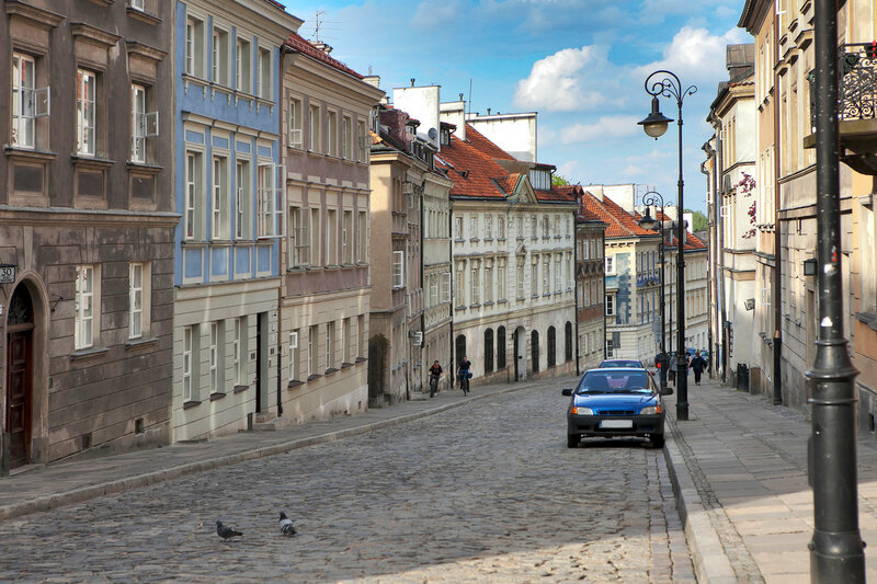 Colorful houses near the fortress wall in the old town in Warsaw. Cherry blooms