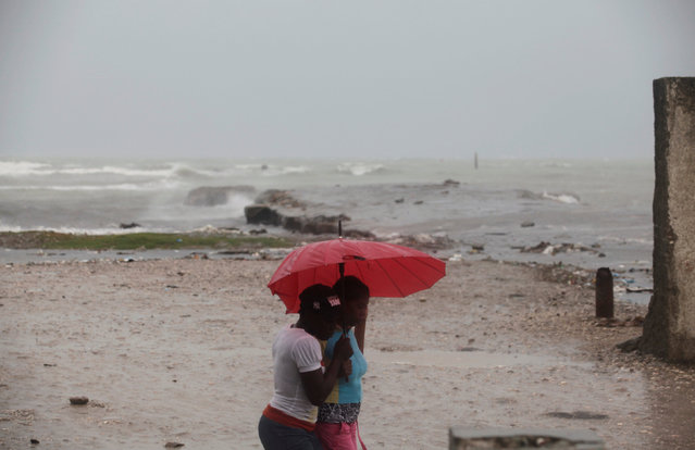 Two women protect themselves from rain with an umbrella ahead of Hurricane Matthew in Les Cayes, Hai