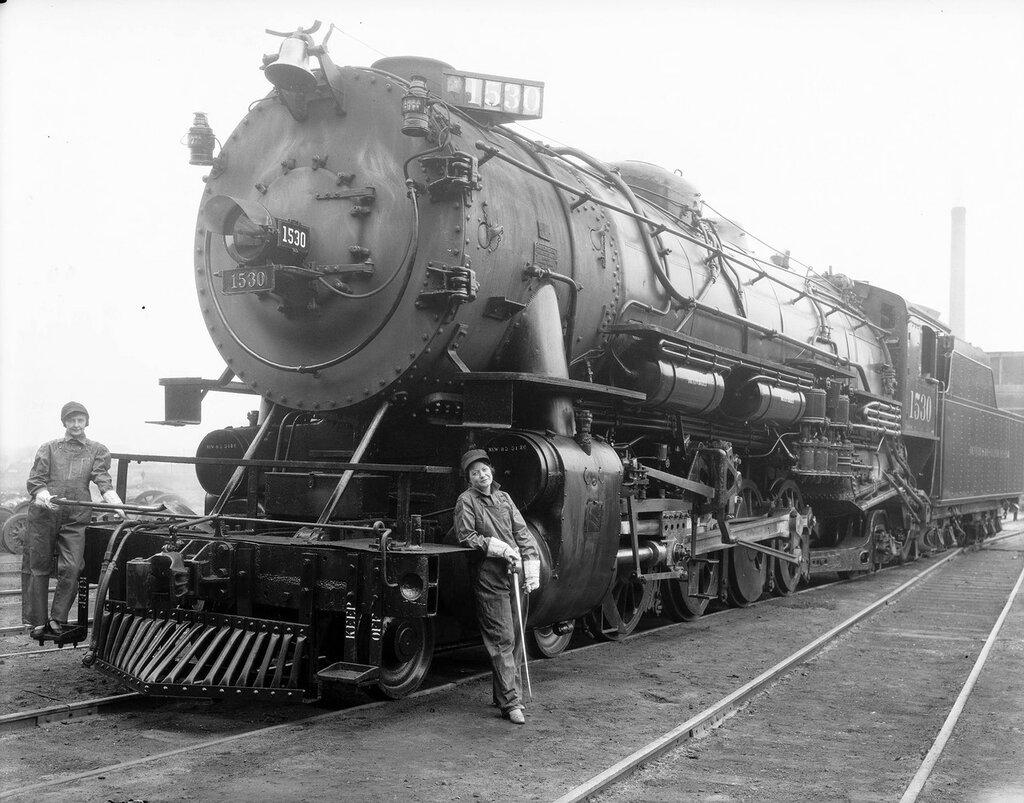 Denver & Rio Grande Western Railroad locomotive 1530 is at Burnham Shops, Denver, Colorado, women in bib overalls and gloves hold a shovel and an oilcan. April, 1926.