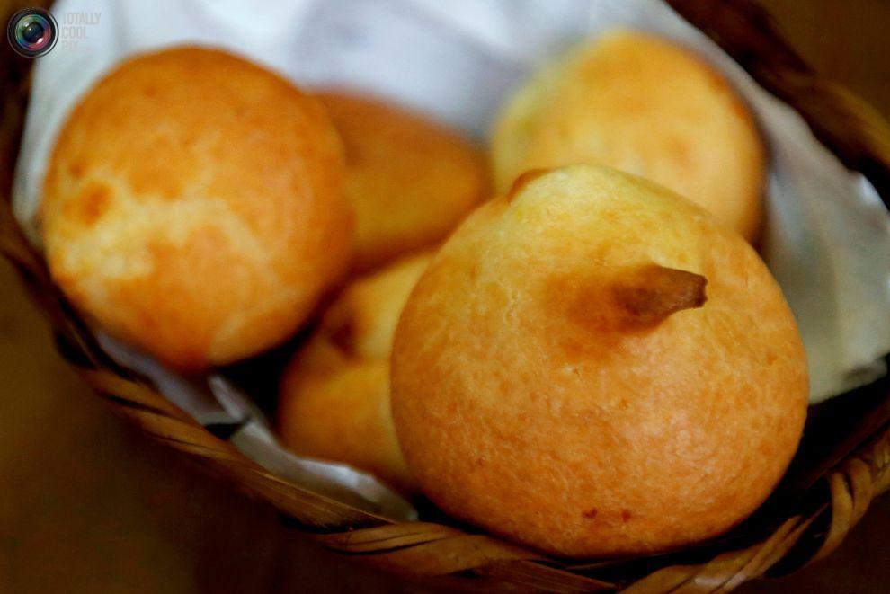 Местные жители обедают традиционными рыбными шариками bolinhos de bacalhau в кафе под открытым небом