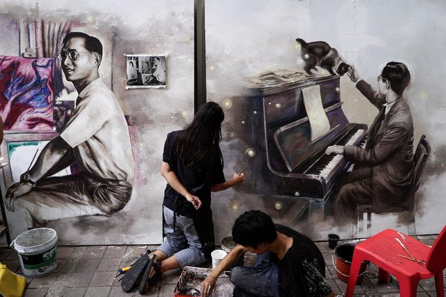Thai art students paint portraits of Thailand's late King Bhumibol Adulyadej at the Silpakorn U
