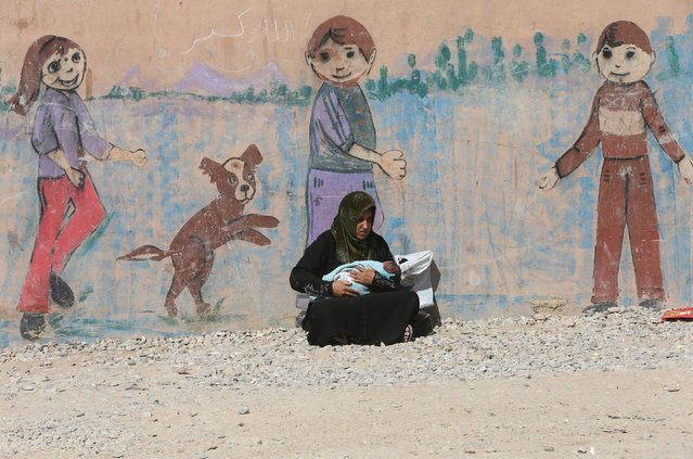 A displaced woman who fled from Islamic State militants in Mosul holds her baby at Deepaka camp in t