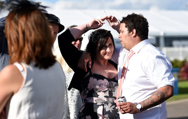Race goers pass a cigarette between each other after the Geelong Cup on Geelong Cup day at Geelong R