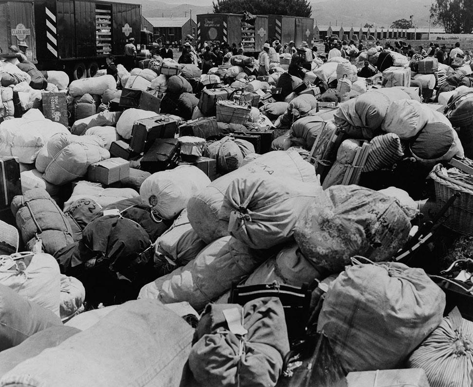 Багаж переселенцев собирают для транспортации в центр сбора в Салинасе, штат Калифорния.