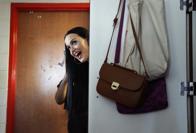 Singer Katy Perry peeks her head around a dorm room door while canvassing for Democratic presidentia