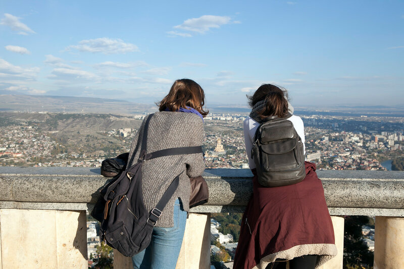 Two girls look with mountains on Tbilisi