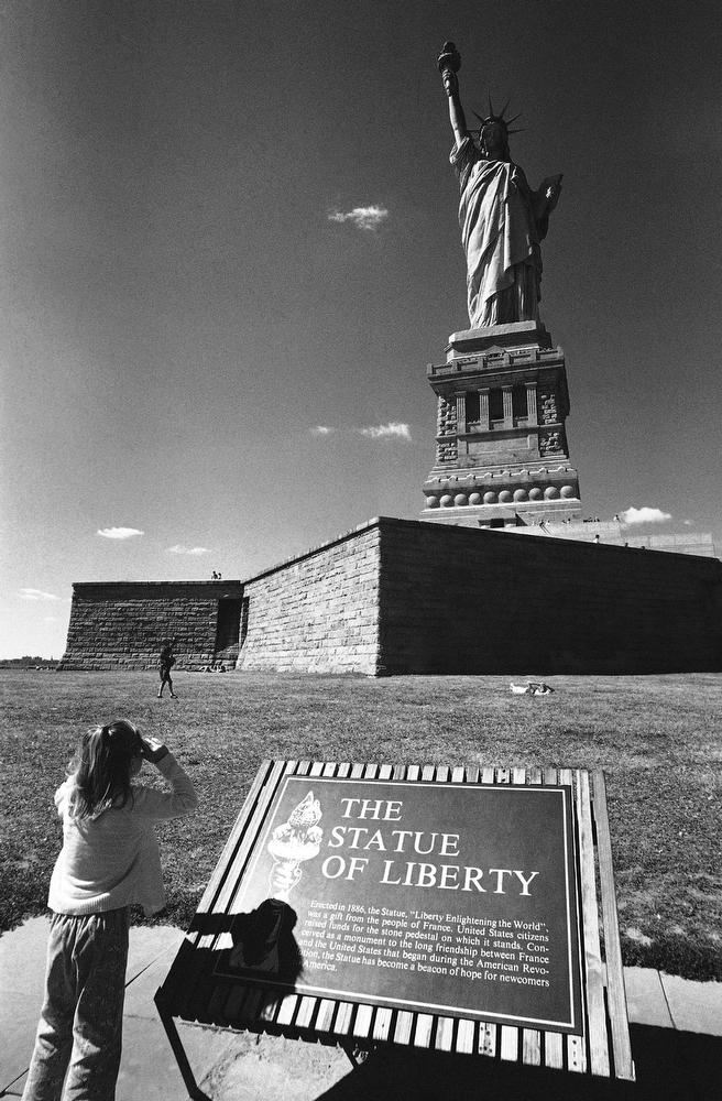36. Девочка фотографирует статую Свободы, 7 сентября 1976 года. Все туристы, приезжающие в Нью-Йорк,