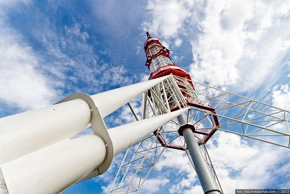 Опоры поддерживают решетчатую конструкцию башни с техническими помещениями и антеннами.