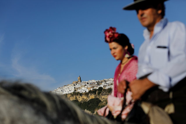 Pilgrims make their way to the shrine of Christ of Romeral as they ride past the white village of Ar