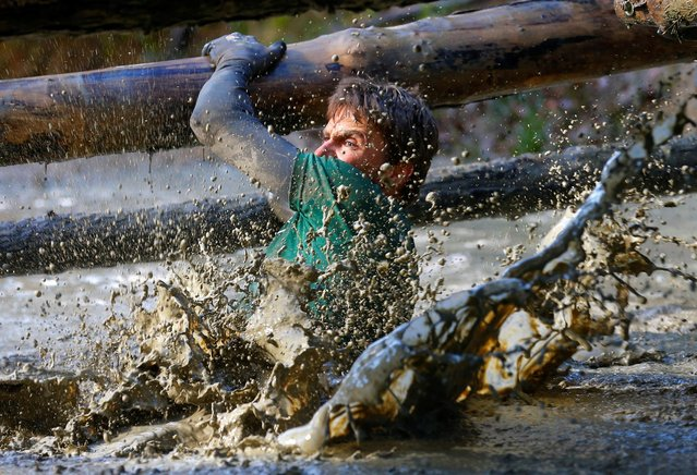 A competitor crosses a water obstacle during the Wildsau Dirt Run (Wild Boar Dirt Run) obstacle cour
