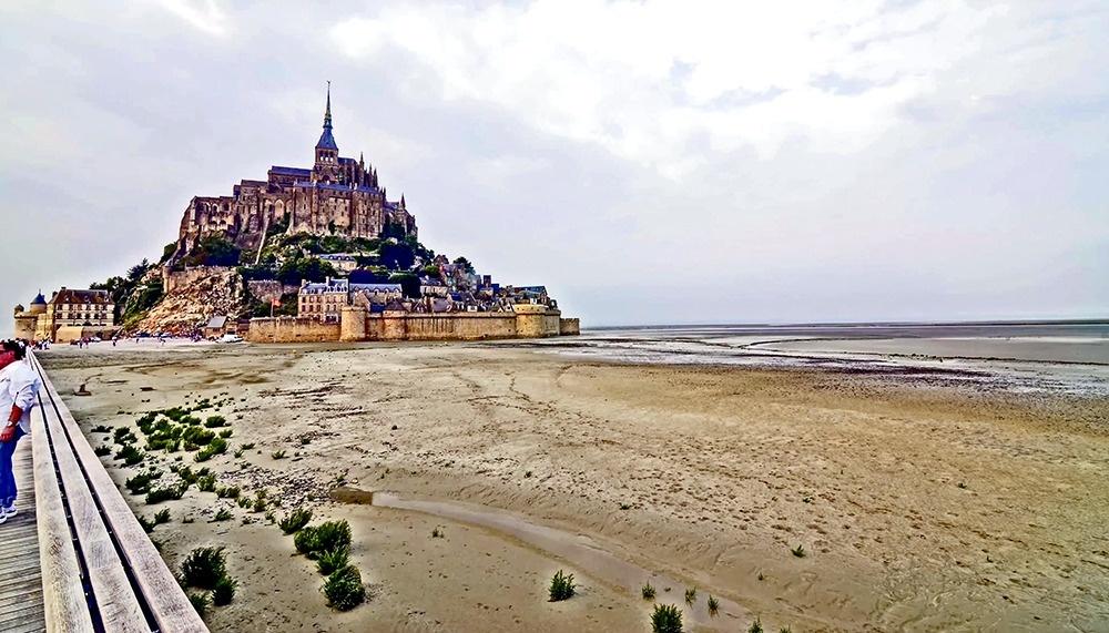 © Giovanni Corigliano  Огромный старинный замок Мон-Сен-Мишель (Mont Saint Michel) выстроен на