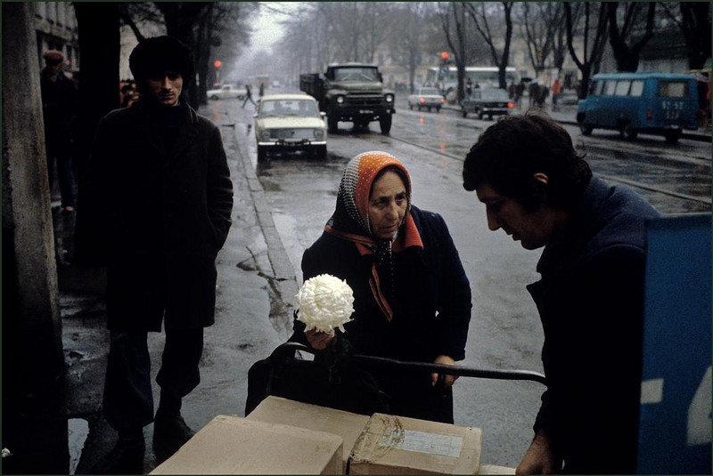 Женщина пытается продать цветы мужчине.