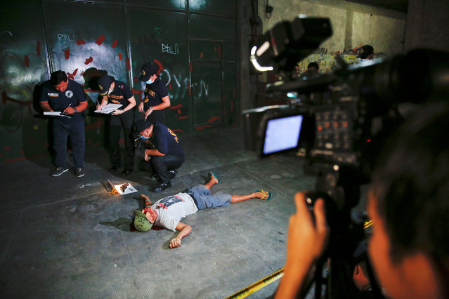Investigators take notes next to the body of a man killed in a shootout with police in Manila, Phili