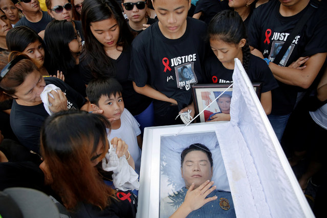 The wife of Rancel Cruz, a police officer killed by an unknown gunman earlier this month, touches th