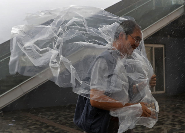 A man braves the wind on the waterfront of Victoria Habour as Typhoon Haima approaches Hong Kong, Fr