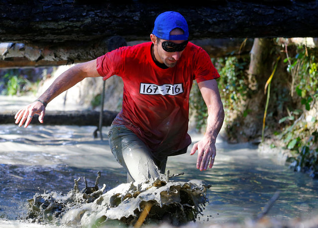 A competitor in costume crosses a water obstacle during the Wildsau Dirt Run (Wild Boar Dirt Run) ob