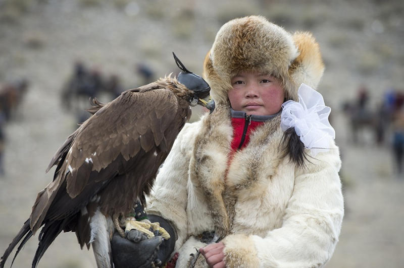 Portrait of a Kazakh teenage girl eagle hunter (winner of 2014 competition) at the Golden Eagle