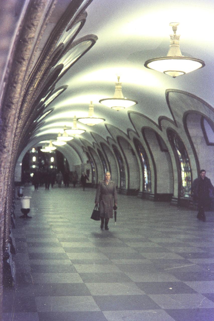 Женщина с зонтиком в зале станции метро