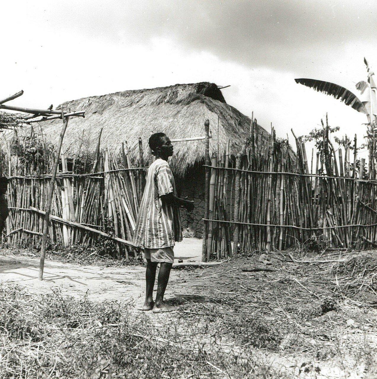 Гана. Деревня в саванне. Местный житель возле огороженной хижины
