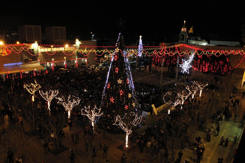 20. Палестинцы смотрят церемонию зажжения рождественской елки на Ясельной площади, у Базилики Рождес