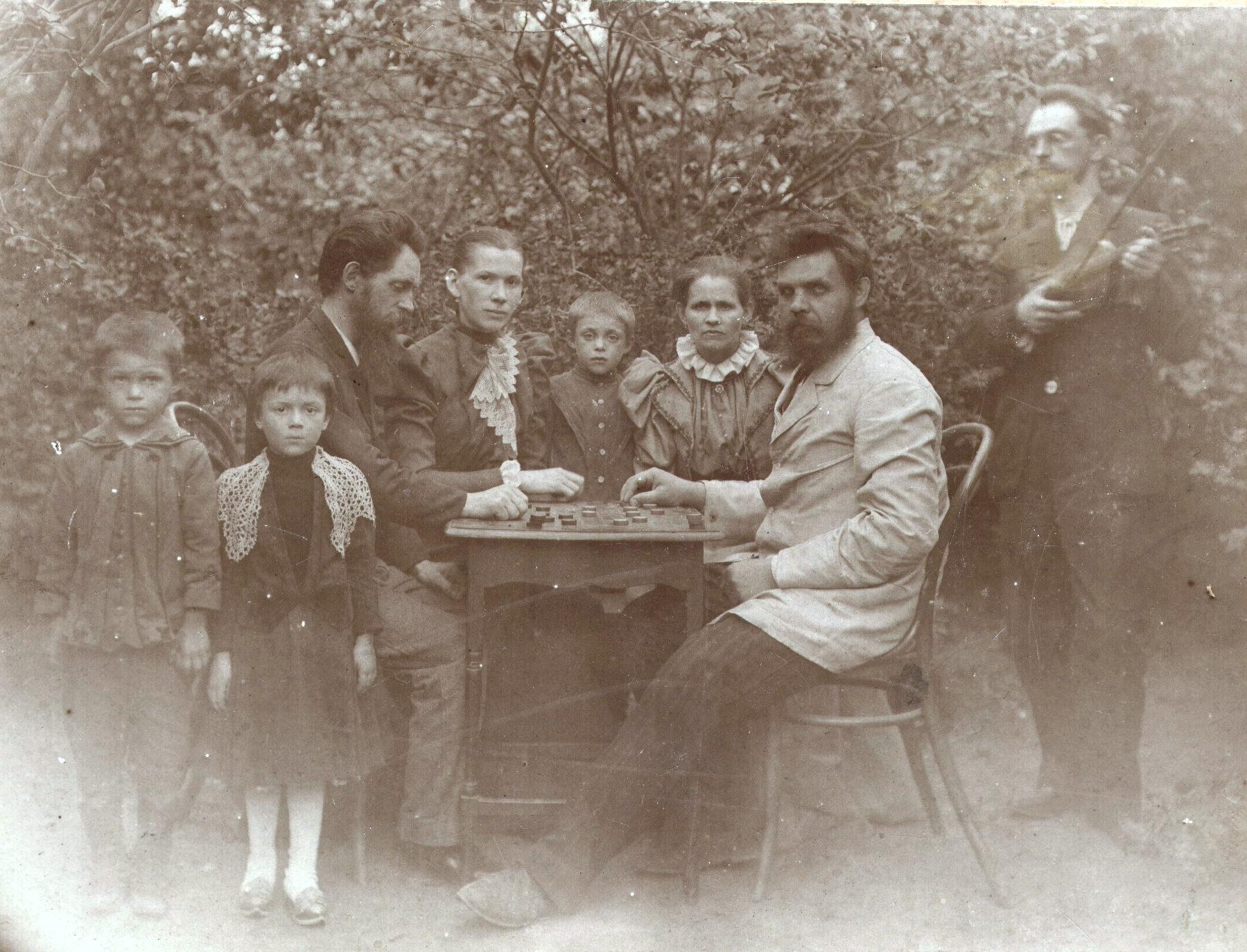 Игра в шашки в саду дома. Слева (сидит за столом) Виктор Петрович Тагунов. Справа стоит музыкант со скрипкой.1910-е