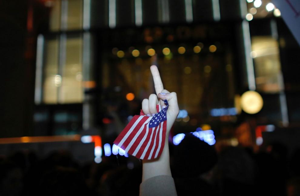 Участница акции протеста в Нью-Йорке против новоизбранного президента Дональда Трампа показывает неп