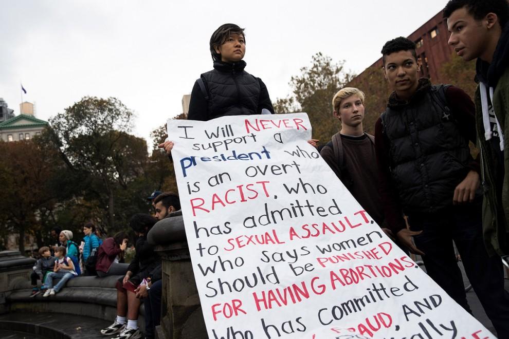 Демонстрантка держит транспарант, на котором перечислены причины, по которым она ни за что на свете