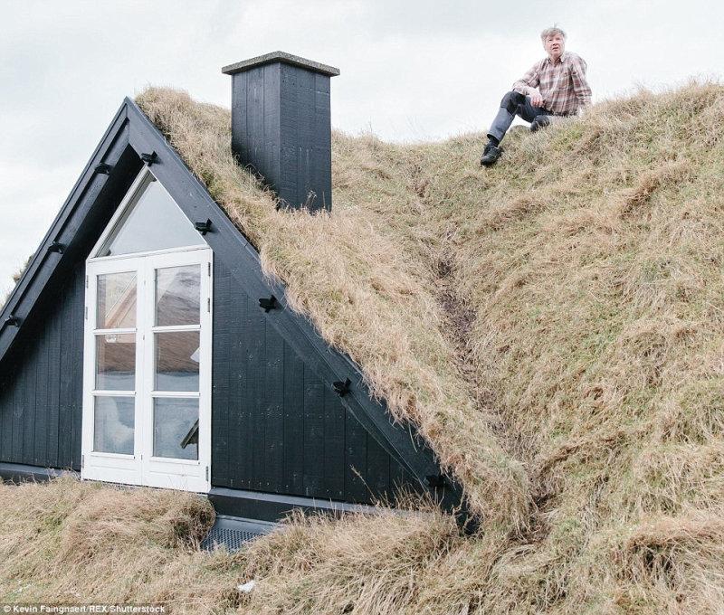 Житель деревни Bour на острове Воар сидит на крыше своего дома. Во время работы над своим про