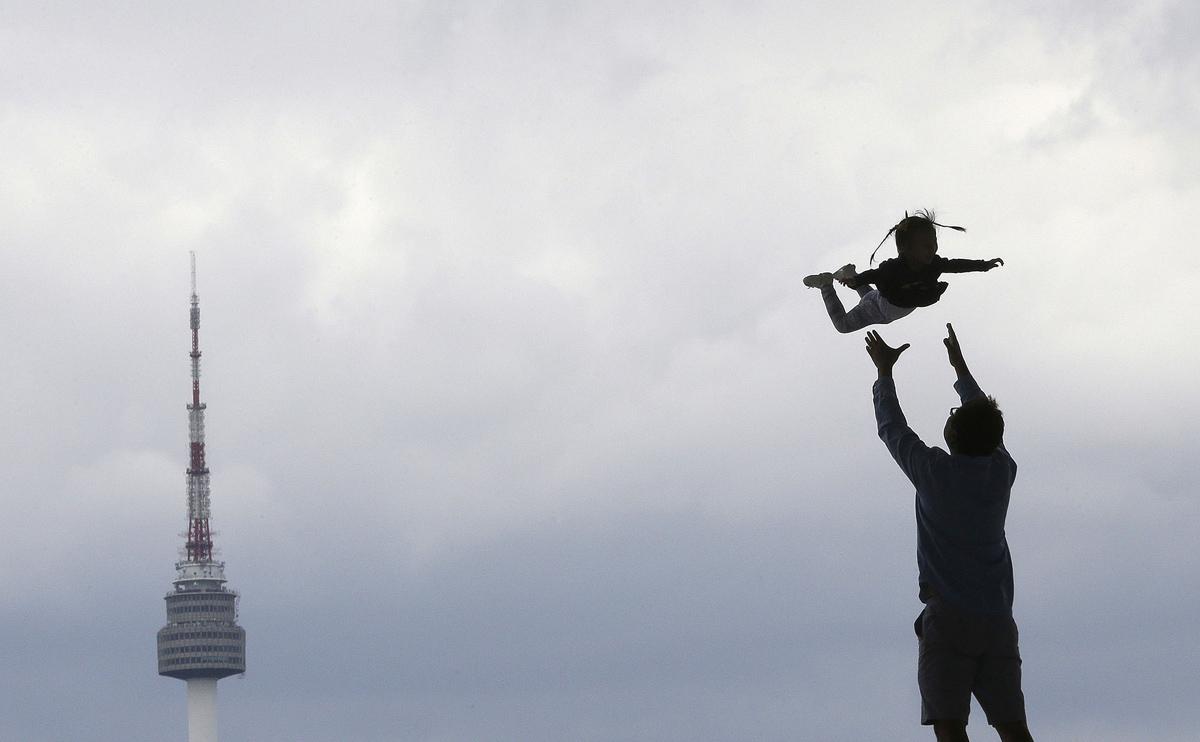 24. Мужчина подбрасывает в воздух свою дочку у Национального музея Кореи, Сеул, 30 августа 2016 года
