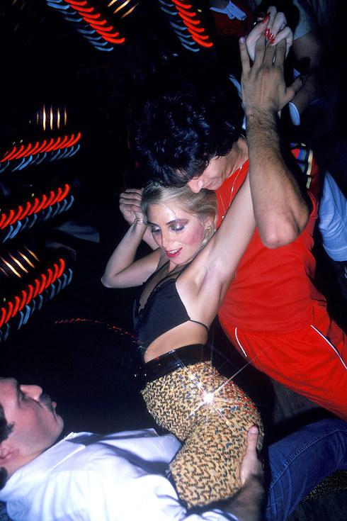 Девушка танцует сразу с двумя мужчинами в клубе Studio 54, 1979 год.