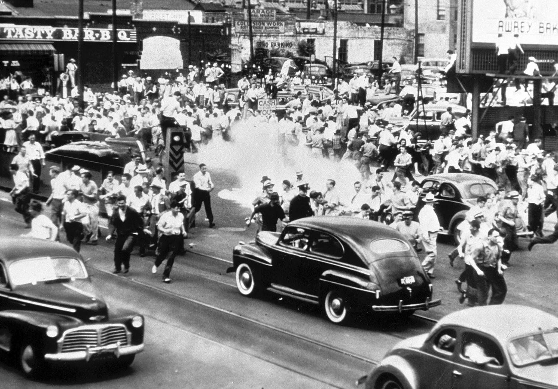 1943. 21 июня. Полиция применяет слезоточивый газ, чтобы разогнать толпу, собравшуюся на главной улице города Детройта, штат Мичиган, в попытке остановить расовые волнения